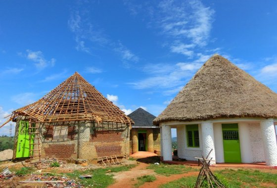 The bottle houses in Uganda - finished and during construction.